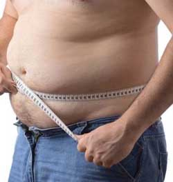 overweight man measuring his body fat with tape measure