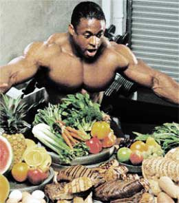 bodybuilder eating lots of food