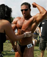 Bodybuilder being oiled before competition.