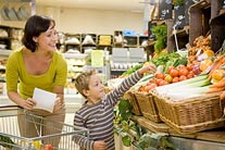 mother grocery shopping with child